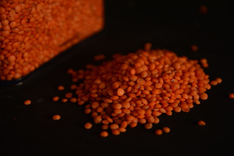 Close-Up Of Red Lentils Against Black Background