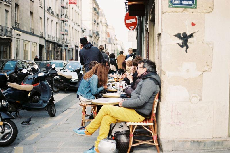 People at sidewalk cafe by street amidst buildings