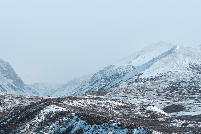Scenic view of snowcapped mountains against clear sky during foggy weather