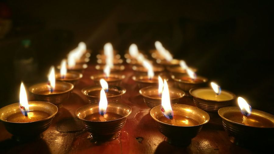 Close-Up Of Illuminated Diyas Arranged On Table In Darkroom