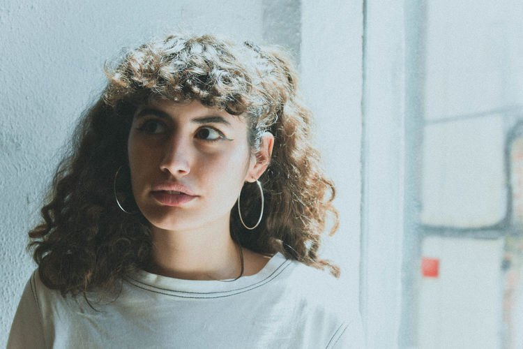 Portrait Headshot One Person Curly Hair Young Adult Real People Hairstyle Hair Front View Lifestyles Looking At Camera Indoors  Wall - Building Feature Young Women Looking Leisure Activity Casual Clothing Beautiful Woman Teenager Contemplation