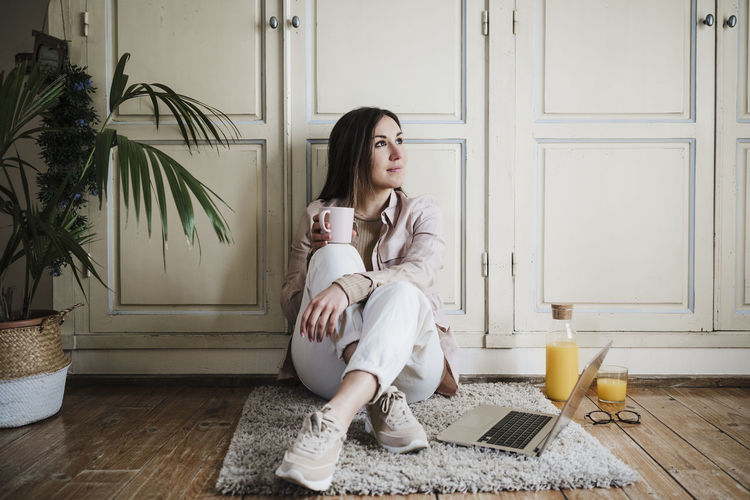 Full length of woman sitting on floor at home