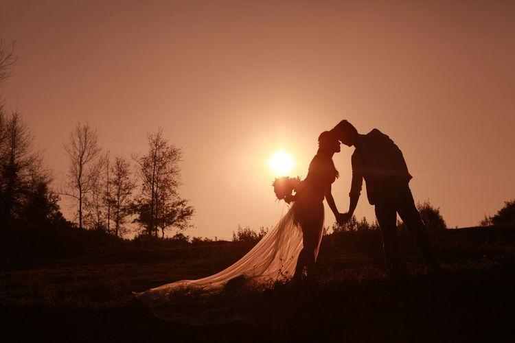 Silhouette bride and bridegroom standing against orange sky