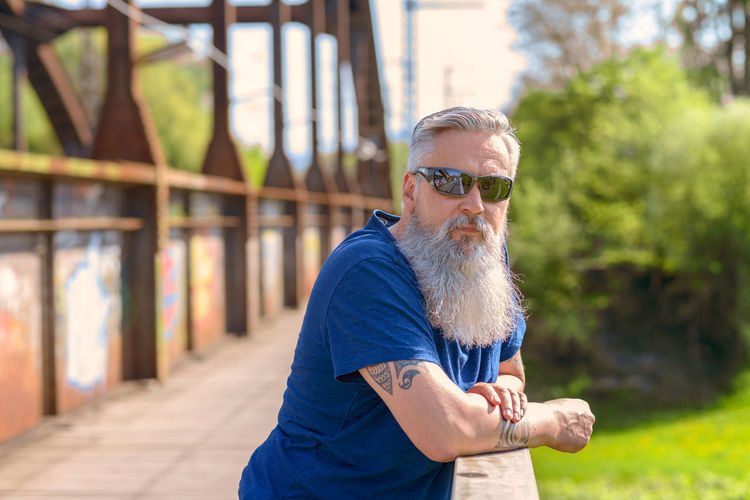 Side view portrait of bearded man wearing sunglasses at park