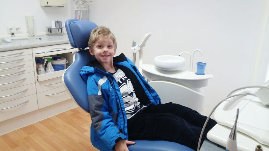 Portrait of boy sitting at dental clinic