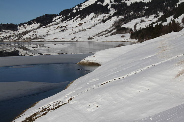 Scenic view of snowcapped mountains by lake during winter