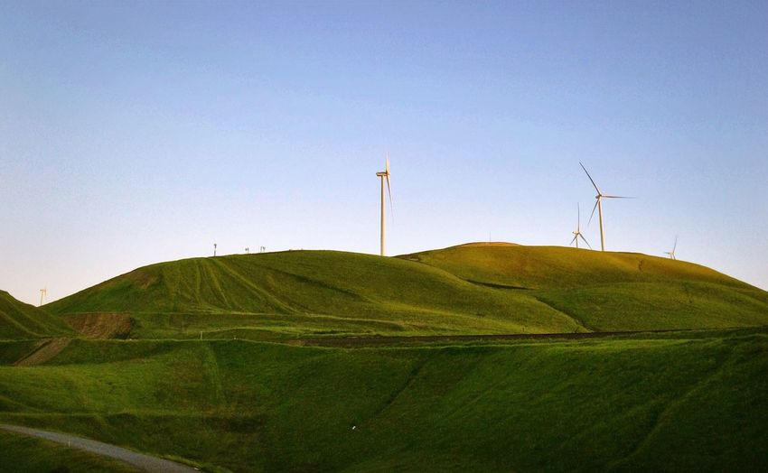 Windmills on green mountain against clear sky