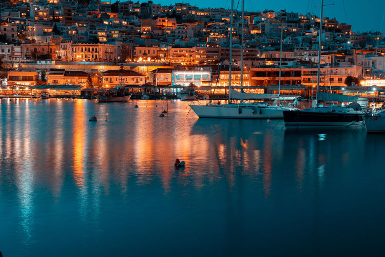 Sailboats in sea by illuminated city buildings