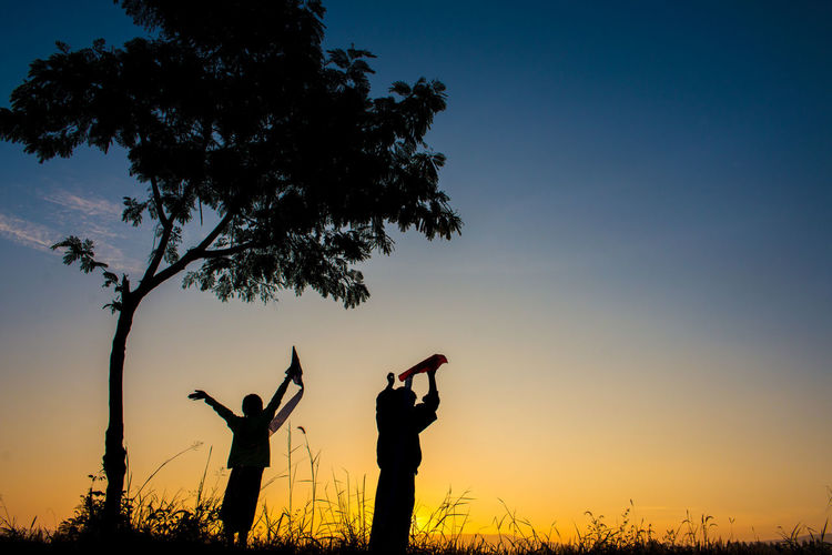 Silhouette boys holding kites while standing on field against sky during sunset