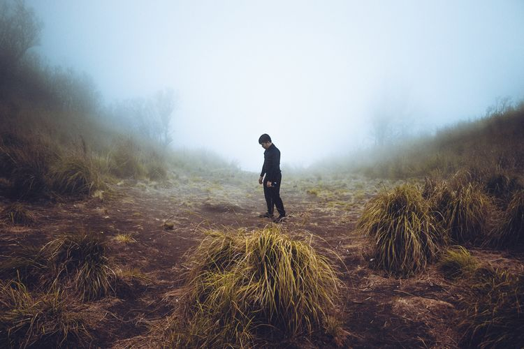 Full length of man standing on land during foggy weather