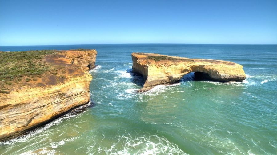 London Arch (formerly London Bridge) is an offshore natural arch formation in the Port Campbell National Park, Australia. The arch is a significant tourist attraction along the Great Ocean Road near Port Campbell in Victoria. This stack was formed by a gradual process of erosion, and until 1990 formed a complete double-span natural bridge. Australia Great Ocean Road Beauty In Nature Clear Sky Drone Photography Horizon Horizon Over Water Land London Arch Natural Arch Nature No People Outdoors Rock Rock - Object Rock Formation Scenics - Nature Sea Sky Solid Stack Rock Tranquil Scene Tranquility Turquoise Colored Water