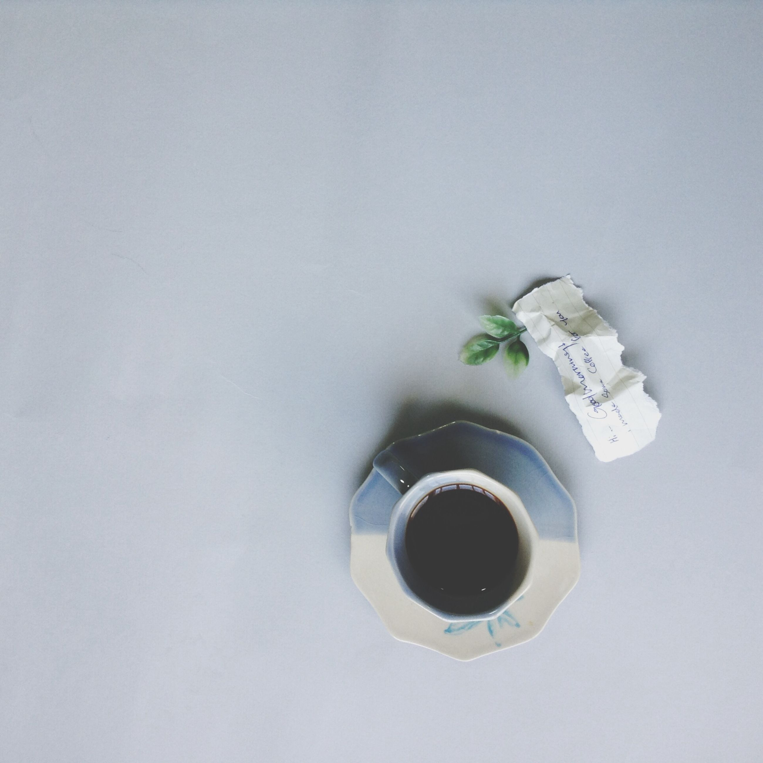 indoors, still life, copy space, white color, white background, studio shot, single object, wall - building feature, table, no people, close-up, coffee cup, directly above, high angle view, white, circle, man made object, metal, built structure, geometric shape