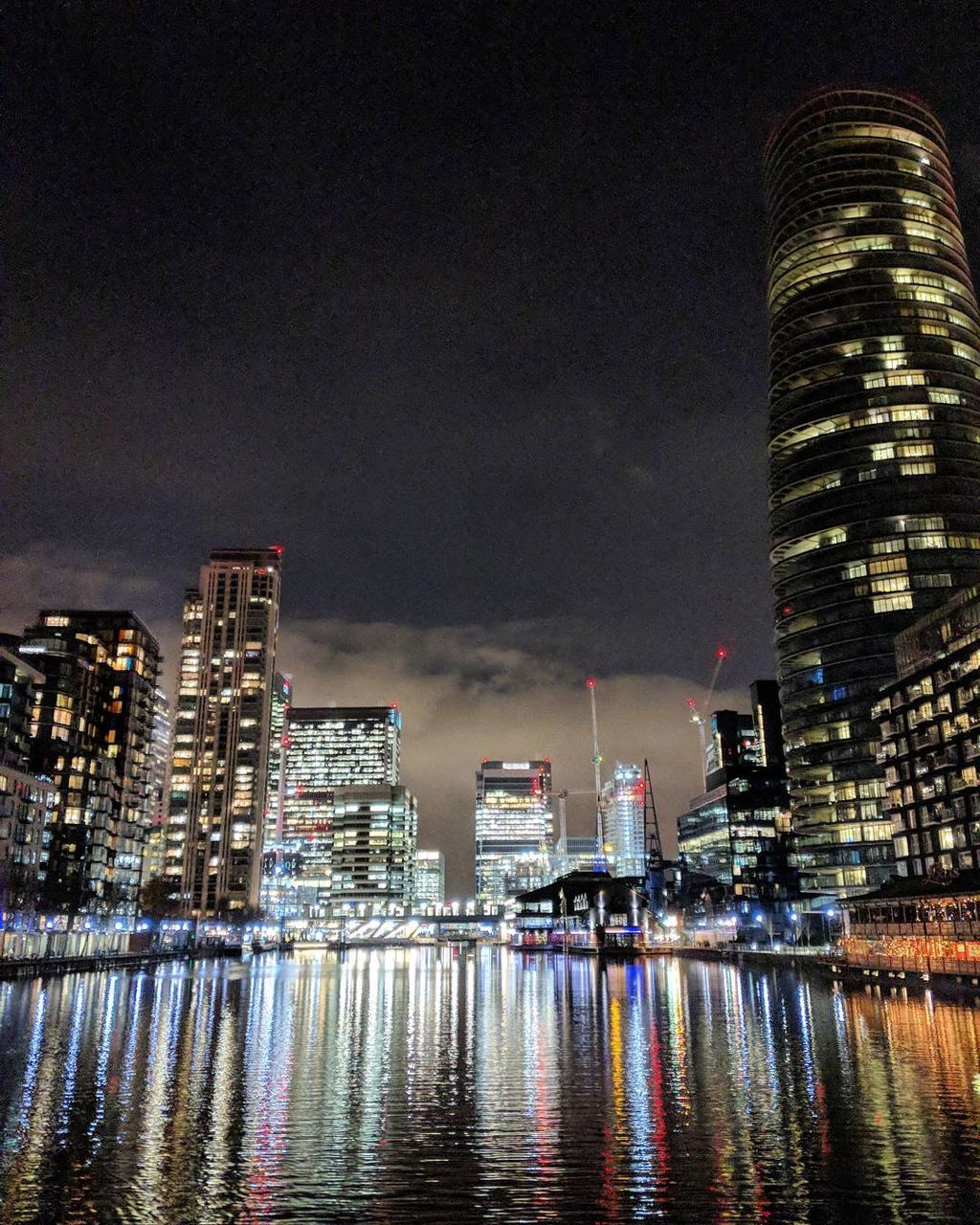 building exterior, architecture, night, built structure, illuminated, skyscraper, city, travel destinations, sky, waterfront, modern, no people, water, tall, cityscape, outdoors, urban skyline