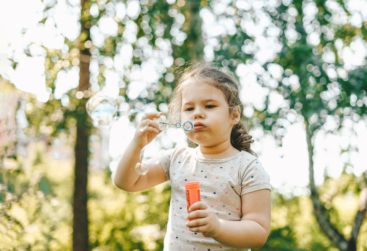 Girl blowing bubbles while standing in park