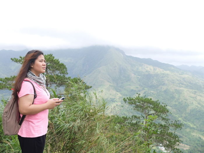 Side View Of Young Woman With Mobile Phone Standing On Mountain Against Sky