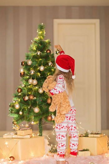 Cute blonde girl 5 years old decorating christmas tree