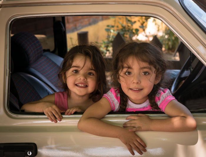 Portrait of smiling girl sitting in car
