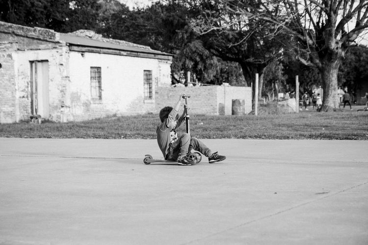 Man sitting on road in city