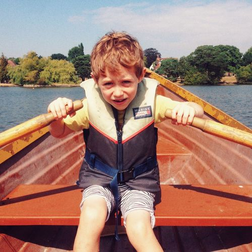 Seven year old boy rowing a boat One Person Leisure Activity Seven Years Old Boy Rowing Boys Real People Front View Lifestyles Portrait Day Outdoors Sky Childhood Water Nature Young Adult