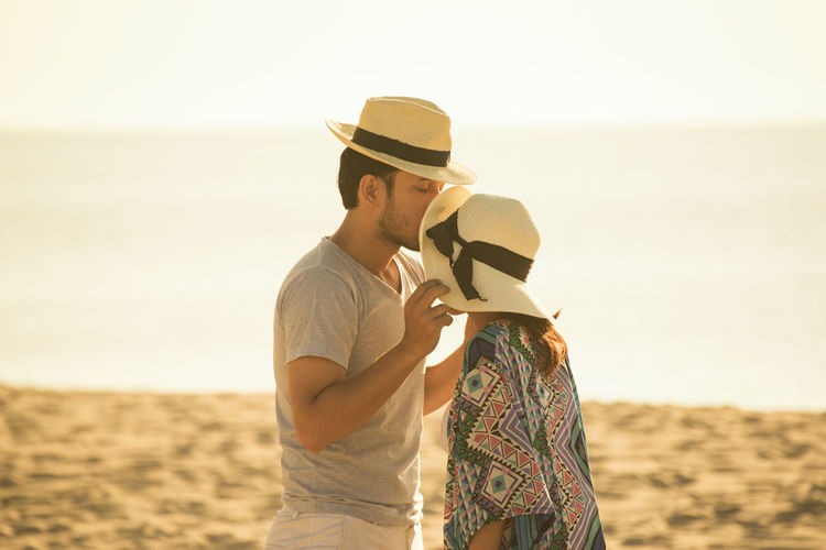 Man kissing on woman forehead at beach against sky