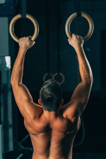 Rear View Of Shirtless Male Athlete Exercising On Gymnastics Rings In Gym