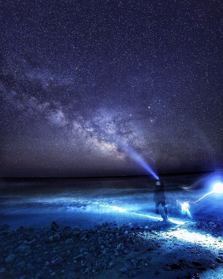 Rear view of person standing on shore holding flashlight against milky way