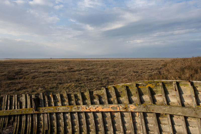 The hull of an abandoned boat frames the view across the salt marshes at Blakeney looking north towards Blakeney Point. Blake And White Norfolk Salt Marsh Wooden Boat Barrier Boat Cloud - Sky Day Environment Horizon Horizon Over Land Land Landscape Nature No People Non-urban Scene Outdoors Protection Rotting Scenics - Nature Sky Structures & Lines Tranquil Scene Tranquility Wood - Material