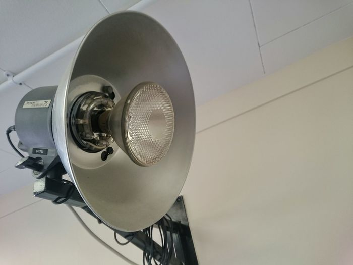 Low angle view of spotlight mounted on wall