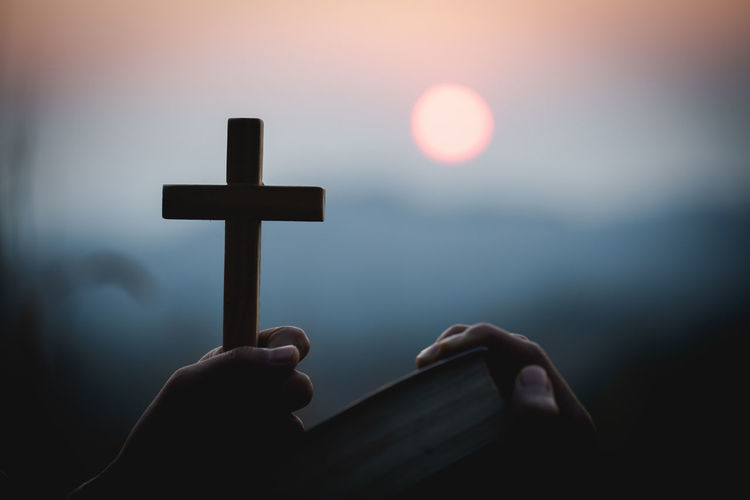 Low angle view of hand holding cross against sky during sunset