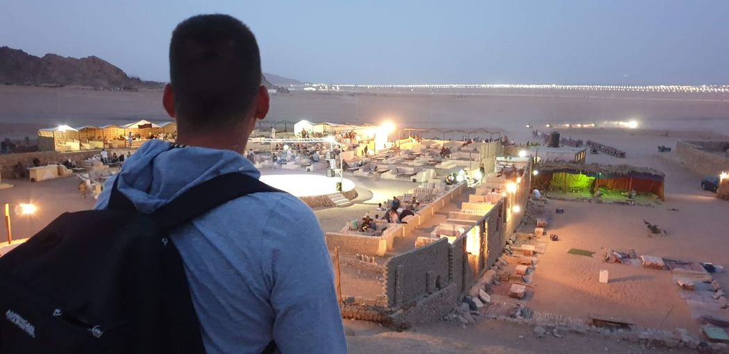 Rear view of man looking at illuminated cityscape against sky