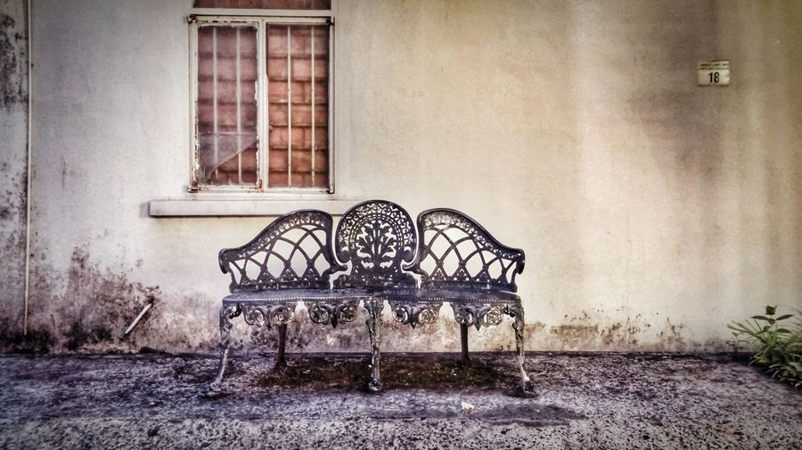 Abandoned Bench Against House