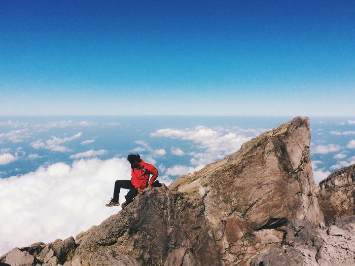 Man standing on rock against blue sky