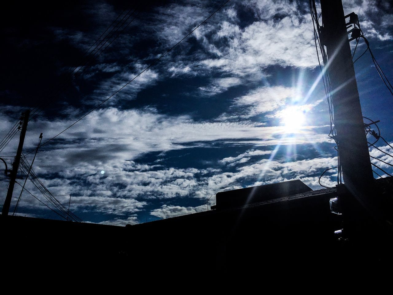 sky, cloud - sky, sunbeam, sunlight, sun, nature, lens flare, architecture, built structure, low angle view, silhouette, outdoors, day, building exterior, beauty in nature, no people, mode of transportation, technology, electricity, bright, power supply