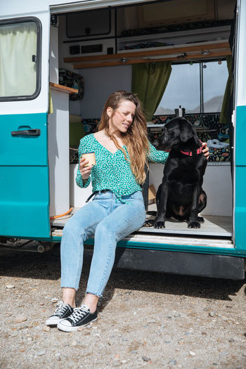 Woman Sitting With Dog In Camper Van