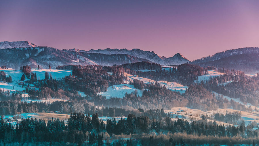 Scenic view of snowcapped mountains against purple sky during sunset
