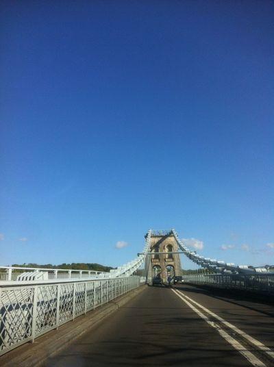 Cars on menai bridge against sky