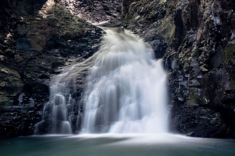 Waterfall flowing on rock formation in forest