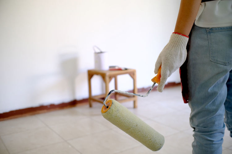 Close-up of woman holding paint roller while standing against wall