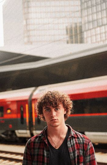 Portrait Of Young Man Standing Against Train