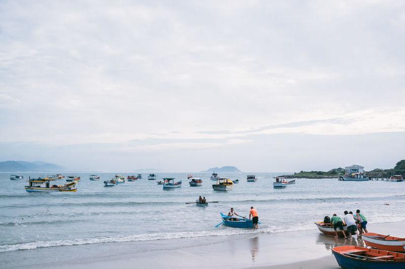 People Sailing On Sea Against Sky