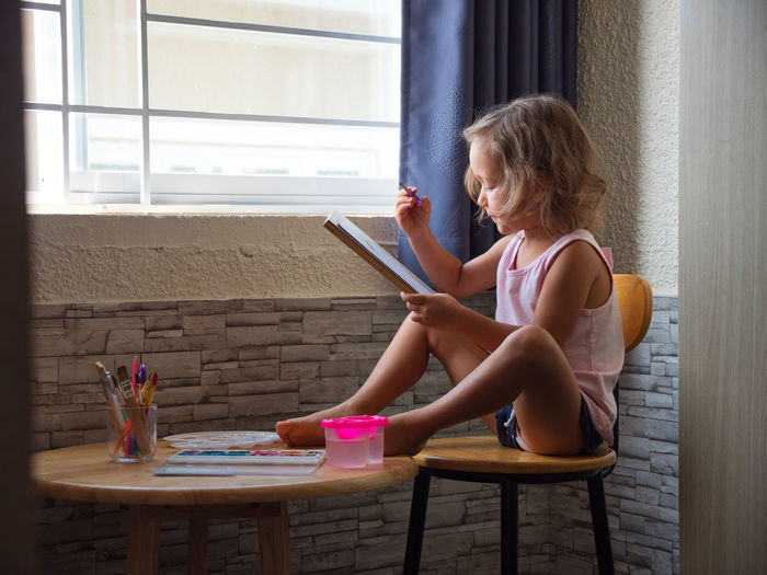 Girl Drawing While Sitting On Stool At Home