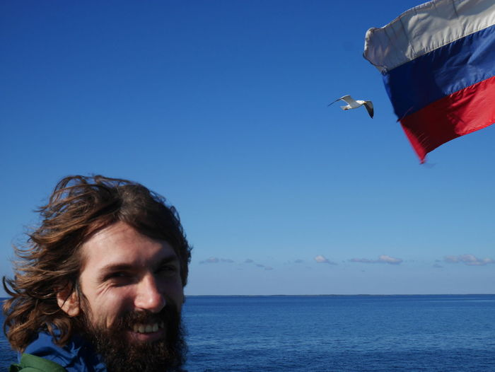 Portrait of man by russian flag against sea