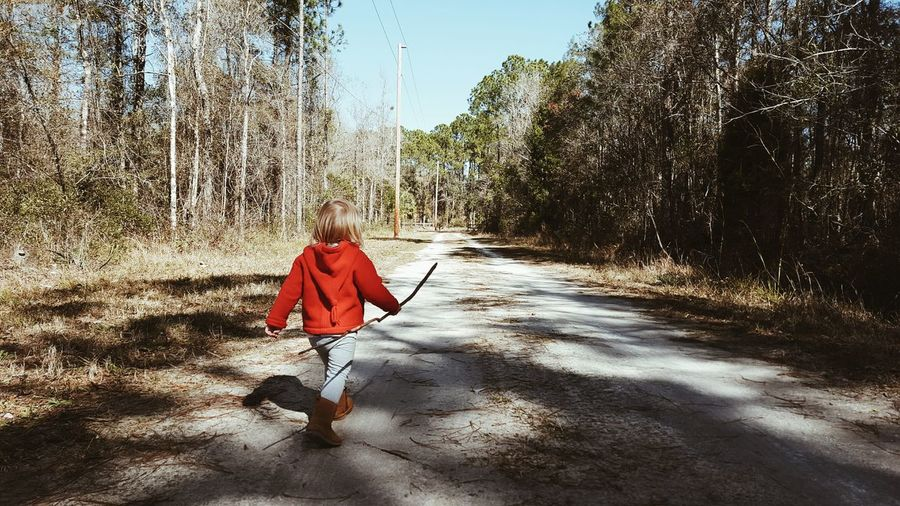Rear view of kid walking on dirt road in forest
