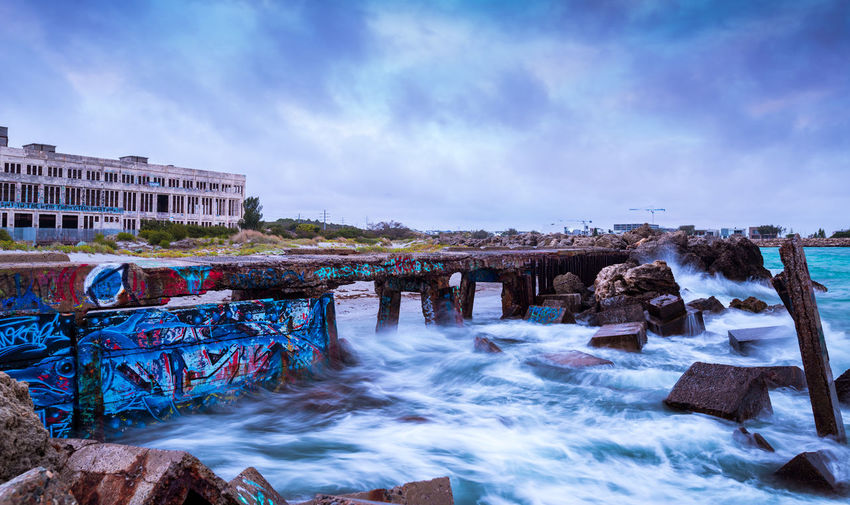 Adbandoned power station Graffiti Ruins Wave Architecture Beauty In Nature Building Exterior Built Structure Cloud - Sky Day Longexposure Motion Nature No People Outdoors Rock - Object Sky Water Shades Of Winter The Graphic City