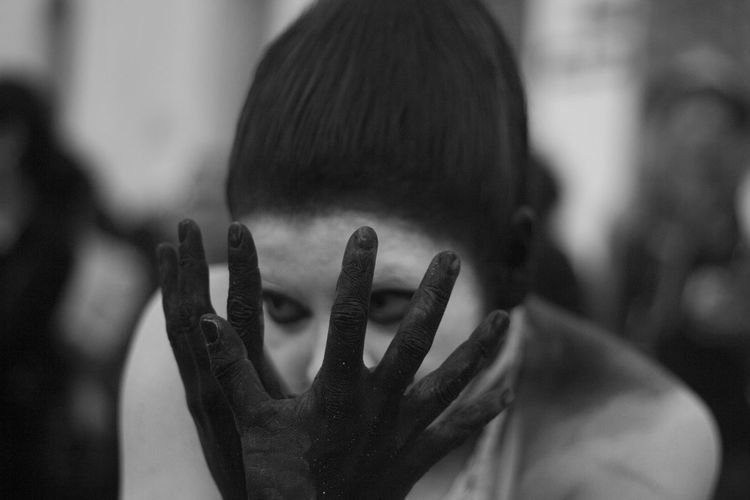 Close-Up Of Woman Covering Face With Black Painted Hands