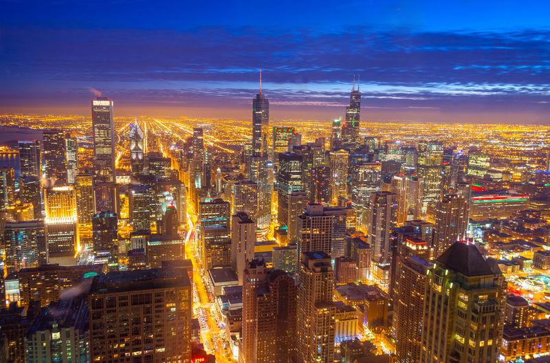 Illuminated cityscape against dramatic sky