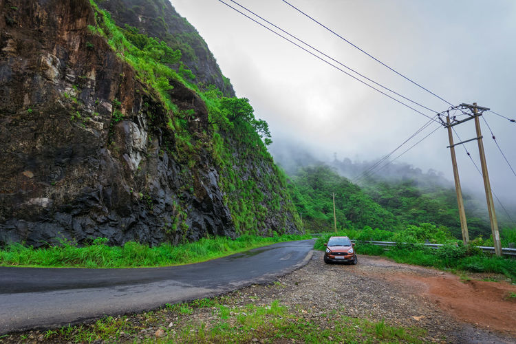 Cars on road by mountain against sky
