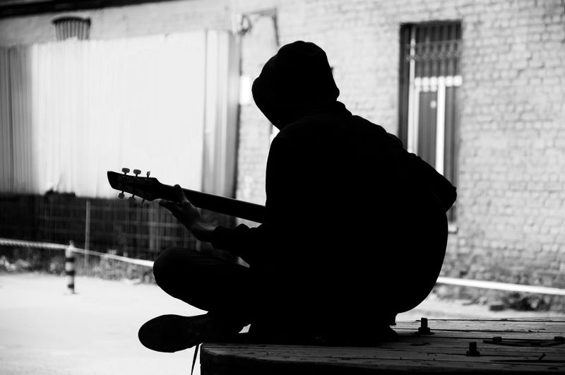 Silhouette teenage boy playing guitar