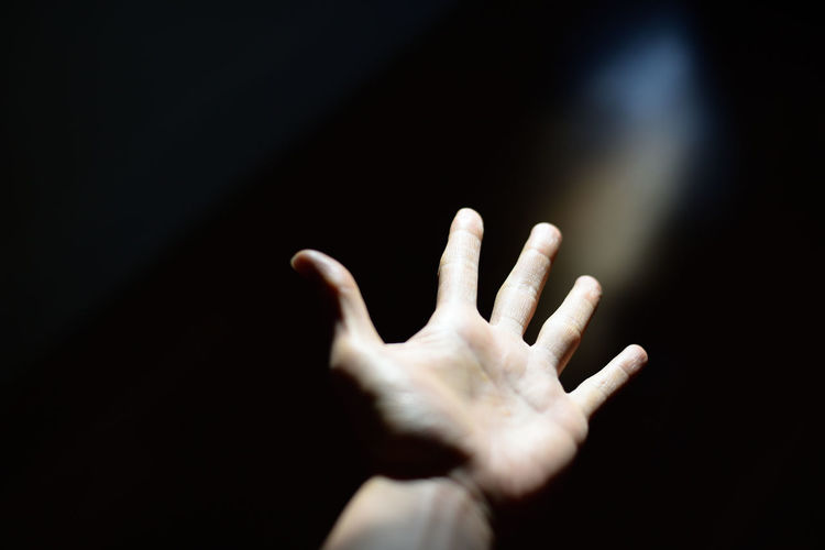 Un moment. Black Background Body Part Close-up Copy Space Dark Domestic Room Finger Hand Human Body Part Human Finger Human Hand Human Limb Indoors  Leisure Activity Lifestyles One Person Real People Studio Shot Sunlight Unrecognizable Person