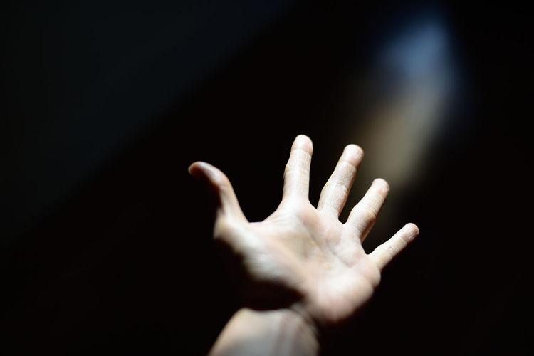 Close-Up Of Hand Gesturing In Darkroom